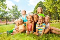 Groep gelukkige kleine jonge geitjes op het gazon in park Royalty-vrije Stock Fotografie