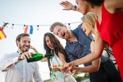 Groep gelukkige mensen of vrienden die pret hebben bij partij royalty-vrije stock afbeeldingen