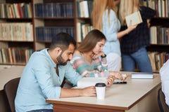 Groep gelukkige studenten die boeken lezen en aan examen in bibliotheek voorbereidingen treffen royalty-vrije stock afbeelding