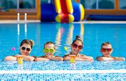 Groep gelukkige tienerjonge geitjes in de pool stock foto