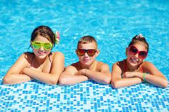 Groep gelukkige tienerjonge geitjes in de pool Stock Afbeelding
