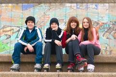 Groep gelukkige tieners in rolschaatsen het zitten Royalty-vrije Stock Afbeeldingen