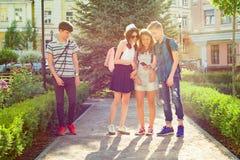 Groep gelukkige tienersvrienden 13 die, 14 jaar langs de stadsstraat lopen royalty-vrije stock afbeelding