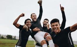 Groep gelukkige voetballers die een winst vieren door hun keeper op te heffen Voetballers die overwinning vieren door hun hand op stock afbeeldingen