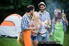 Groep gelukkige vrienden die barbecuepartij in bos hebben stock foto's