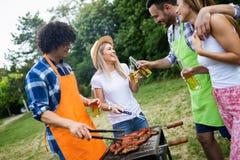 Groep gelukkige vrienden die en bieren eten drinken bij barbecuediner royalty-vrije stock afbeelding