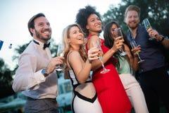 Groep gelukkige vrienden die en dranken partying roosteren royalty-vrije stock afbeelding