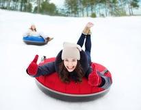 Groep gelukkige vrienden die neer op sneeuwbuizen glijden Stock Afbeelding