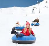Groep gelukkige vrienden die neer op sneeuwbuizen glijden Royalty-vrije Stock Foto