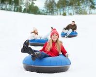 Groep gelukkige vrienden die neer op sneeuwbuizen glijden Royalty-vrije Stock Foto's