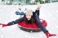 Groep gelukkige vrienden die neer op sneeuwbuizen glijden Royalty-vrije Stock Fotografie