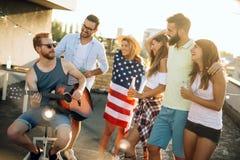 Groep gelukkige vrienden die partij op dak hebben stock afbeeldingen