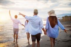 Groep gelukkige vrienden die pret hebben die onderaan het strand bij zonsondergang lopen royalty-vrije stock foto