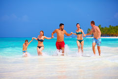 Groep gelukkige vrienden die samen op tropisch strand lopen stock foto's