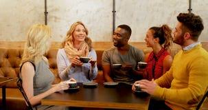 Groep gelukkige vrienden die terwijl het hebben van koffie 4K 4k op elkaar inwerken stock videobeelden