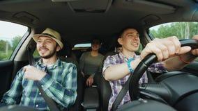 Groep gelukkige vrienden in en auto die terwijl de reis van de aandrijvingsweg zingen dansen Stock Foto