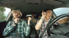 Groep gelukkige vrienden in en auto die terwijl de reis van de aandrijvingsweg zingen dansen stock footage