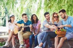 Groep gelukkige vrienden met gitaar Terwijl één van hen gitaar speelt en anderen geven hem een ronde van applaus royalty-vrije stock afbeeldingen