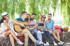 Groep gelukkige vrienden met gitaar Terwijl één van hen gitaar speelt en anderen geven hem een ronde van applaus royalty-vrije stock foto