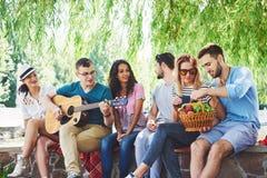 Groep gelukkige vrienden met gitaar Terwijl één van hen gitaar speelt en anderen geven hem een ronde van applaus royalty-vrije stock afbeelding