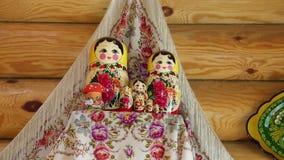 Groep genestelde poppen op een plank in de achtergrondhanddoeken en de houten muur stock video