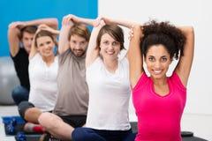 Groep geschikte jonge vrienden die bij de gymnastiek uitoefenen Stock Foto's