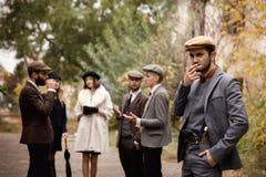 Groep gevaarlijke retro gangsters in het park, het roken royalty-vrije stock foto's