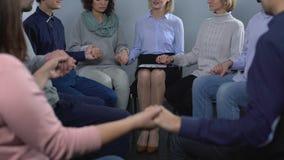 Groep gewijde mensen die in cirkel zitten en handen houden bij therapiezitting stock videobeelden