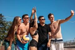 Groep glimlachende Europese vrienden die selfie op strand maken stock foto