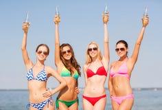 Groep glimlachende jonge vrouwen die op strand drinken royalty-vrije stock afbeeldingen