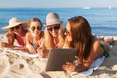 Groep glimlachende jonge vrouwen met tabletten op strand Stock Foto's