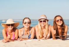 Groep glimlachende jonge vrouwen met tabletten op strand Stock Fotografie