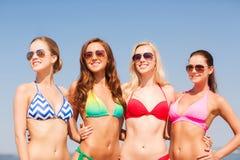 Groep glimlachende jonge vrouwen op strand Stock Foto