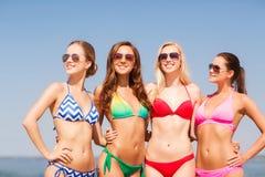 Groep glimlachende jonge vrouwen op strand Stock Afbeeldingen