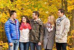 Groep glimlachende mannen en vrouwen in de herfstpark Stock Foto's