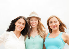 Groep glimlachende meisjes die op het strand koelen Stock Afbeelding