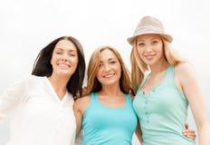 Groep glimlachende meisjes die op het strand koelen Stock Afbeeldingen