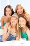 Groep glimlachende meisjes in koffie op het strand Stock Afbeeldingen
