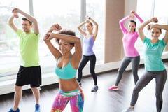 Groep glimlachende mensen die in gymnastiek of studio dansen Stock Afbeelding