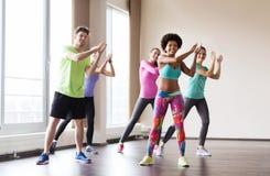 Groep glimlachende mensen die in gymnastiek of studio dansen Stock Foto