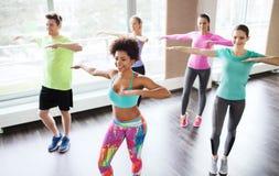 Groep glimlachende mensen die in gymnastiek of studio dansen Stock Foto's