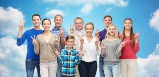 Groep glimlachende mensen die het teken van de vredeshand tonen Stock Fotografie