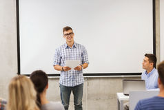 Groep glimlachende studenten en leraar in klaslokaal Stock Foto's