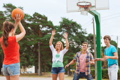 Groep glimlachende tieners die basketbal spelen Stock Foto