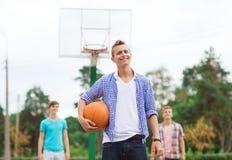 Groep glimlachende tieners die basketbal spelen royalty-vrije stock afbeeldingen