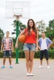 Groep glimlachende tieners die basketbal spelen Stock Afbeelding