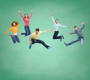 Groep glimlachende tieners die in lucht springen Stock Foto's