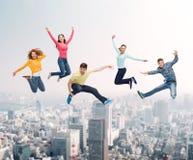 Groep glimlachende tieners die in lucht springen Stock Afbeeldingen