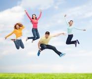 Groep glimlachende tieners die in lucht springen Royalty-vrije Stock Afbeelding