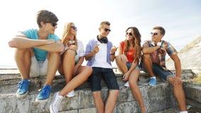 Groep glimlachende tieners die uit in openlucht hangen stock videobeelden